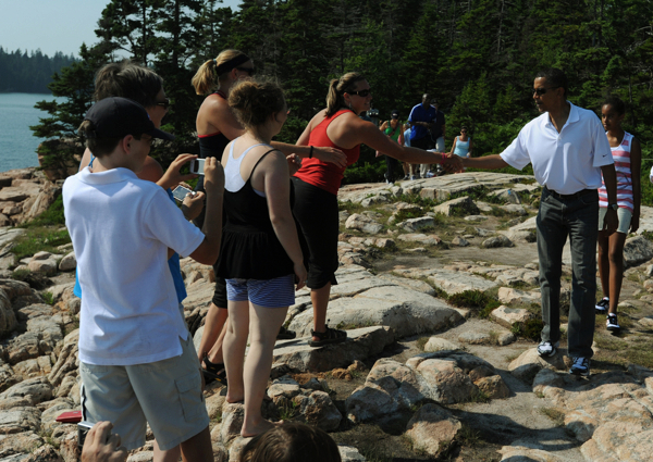 President Barack Obama greets tourist and locals including Elizabeth Jury of DeWitt Michigan (red shirt) and fellow tourist Brittany Wilkins (wearing headband)  as he hikes along the Ship Harbor Trail in Acadia National Park on Saturday, July 17, 2010.