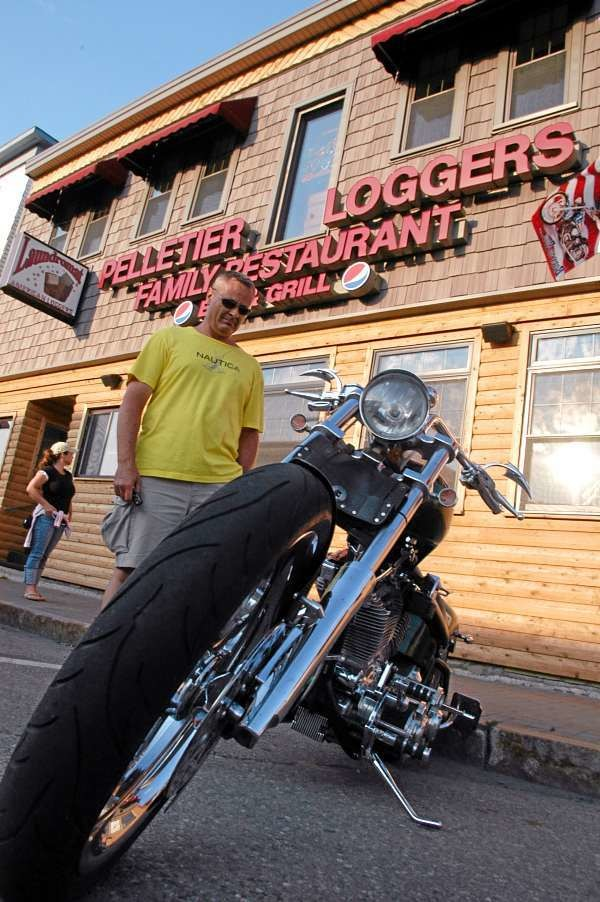 Millinocket native Shawn Tardy, 43, of Washington, D.C. examines a Harley-Davidson motorcycle at the Pelletier Loggers Family Restaurant Bar and Grill?s Millinocket Bikers Weekend on Saturday. His wife Stacy Tardy, 37, is behind him. BANGOR DAILY NEWS PHOTO BY NICK SAMBIDES JR.