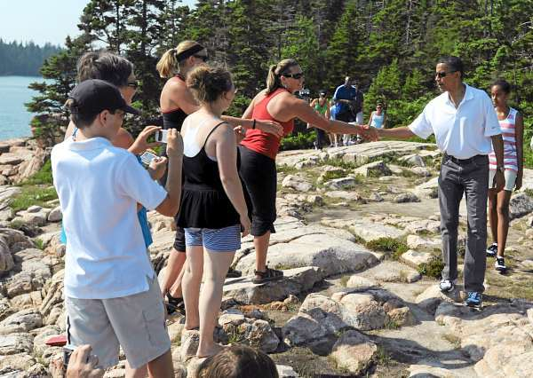 Walking with his daughter, Malia, President Barack Obama greets tourists including Elizabeth Jury of DeWitt, Michigan (red shirt) and  Brittany Wilkins (wearing headband) of Arlington, Nebraska, as the first family hikes along the Ship Harbor Trail in Acadia National Park on Saturday, July 17, 2010. Taking  photos in the foreground are George Mitchell and his mother, Karen  Mitchell, of Standish. The woman with the black and white top is unidentified. (Bangor Daily News/Kevin Bennett)