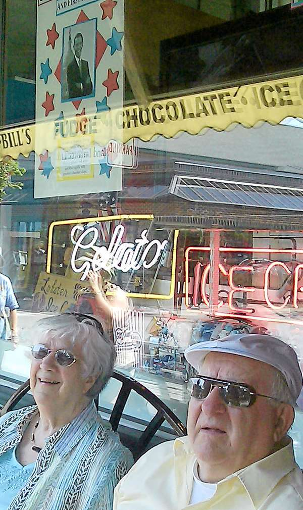 Jennie and Raynald Martin of Brewer sit Saturday afternoon outside Ben & Bill's ice cream shop in downtown Bar Harbor below a homemade poster of Barack Obama taped up in the shop window. The Martins usually visit Bar Harbor once a month and were hoping to catch a glimpse of the president and his family, who are vacationing on MDI for the weekend. The Martins, who said they shook John F. Kennedy's hand when he made a campaign appearance in Waterville in 1960, said they were impressed Obama and his family had come to Bar Harbor. &quotI think it's fantastic,&quot Raynald Martin said. &quotI wish we could have seen him.&quot (Bangor Daily News/Bill Trotter)