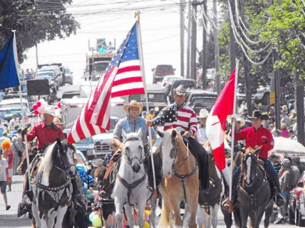 w/ a story slugged POTFEST, LYNDS, FORT FAIRFIELD: POTFEST 1, CUT LINE, FORT FAIRFIELD: Flag bearers on horseback took the lead in the processsional during the 63rd annual Maine Potato Blossom Festival parade on Saturday, July 17. Thousands of people lined the streets of the community for the nearly two hour long parade. (BANGOR DAILY NEWS PHOTO BY JEN LYNDS)