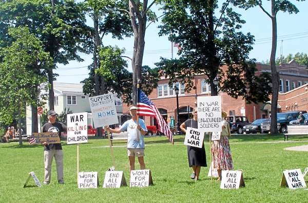 Members of the Bar Harbor Peace Vigil send a message to President Obama on the Village Green in Bar Harbor Saturday, urging him to bring the troops and the war dollars home.  (Bangor Daily News Photo by Rich Hewitt)