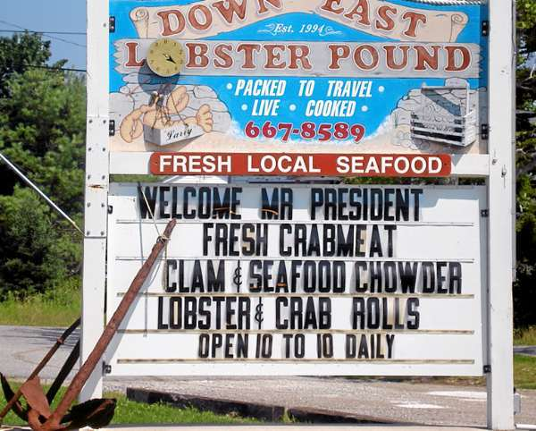 Signs around the Bar Harbor area welcome the President and his family:  Obama gets top billing over the boiled lobsters and other offerings at the Downeast Lobster Pound in Trenton. (Bangor Daily News Photo by Rich Hewitt)