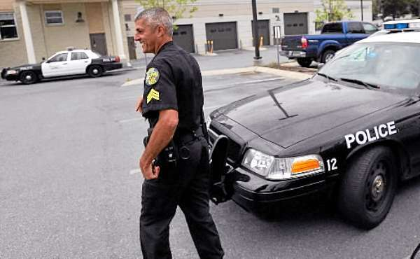 Sgt. Paul Edwards heads back to the Bangor Police Dept. from his squad car Monday afternoon. July 19, 2010 . The Bangor City Council is meeting Monday, July 19, 2010 to talk about hiring a consultant to look at police department operations. (Bangor Daily News/John Clarke Russ)