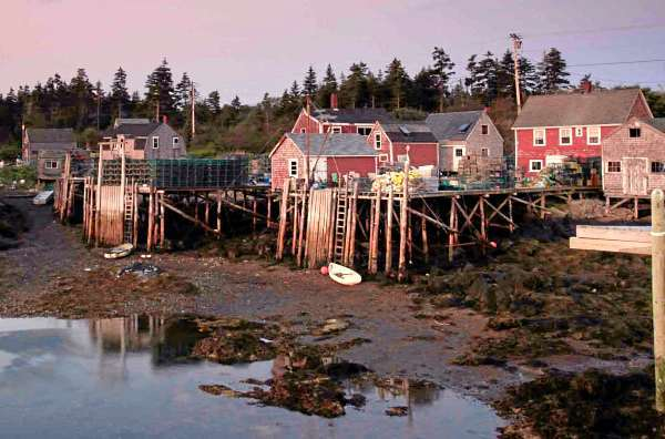 File-In this Aug. 19, 2009 file photo, fishing wharves are seen at low tide at dawn on Matinicus Island, Maine. Maine's lobstermen have long lived under unofficial territorial rules dictating who can set their lobster traps where along the state's long, ragged coast. To protect lucrative fishing grounds, fishermen have been known to cut lobster trap lines, harass each other at sea and, on occasion, brandish weapons. (AP Photo/Robert F. Bukaty/file)