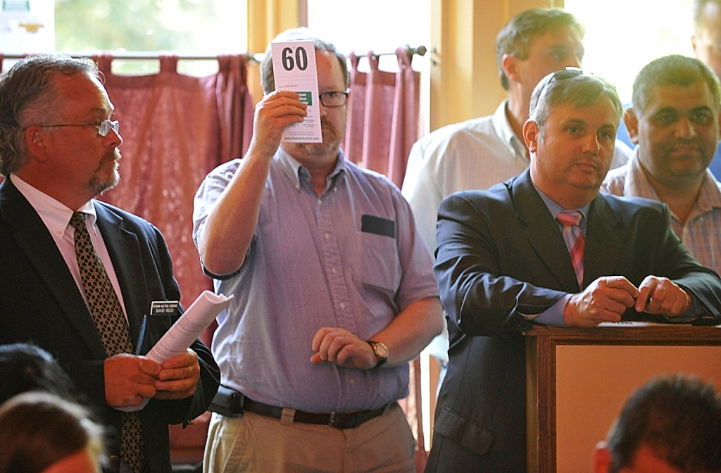 A bidder raises his card during Wednesday's real estate auction of the Whig & Courier's restaurant facilty and equipment. Dan Sykes of Bangor had the highest bid at $355,000. (Bangor Daily News/John Clarke Russ)