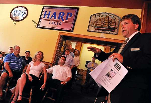 Stefan Keenan (cq), right, real estate division manager with South Portland-based Keenan Auction Company, lays down the ground rules for attendees before the opening bids for the Whig & Courier's restaurant facility and equipment Wednesday morning, July 21, 2010. The highest bid was $355,000. (Bangor Daily News/John Clarke Russ)