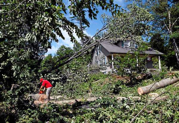 A man clears fallen trees that damaged a home following a severe storm, Thursday, July 22, 2010, in Gorham, Maine.  The storm, which triggered tornado warnings, knocked out power to 22,000 residents, flooded roads, damaged homes and uprooted trees across southern and coastal Maine. (AP Photo/Robert F. Bukaty)