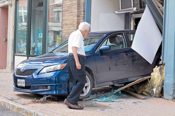 A woman apparently trying to parallel-park in front of the Top Shelf Coins & Comics Thursday morning somehow ended up inside the shop on Central Street in Bangor.  Everett Leighton, who has a jewelry repair shop a few doors away, surveys the demolished storefront and window displays.  The store was not open at the time of the accident and no one was hurt.  (Photo courtesy of Lawrence Whittemore)