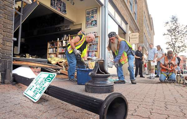 City of Bangor employees clean up the debris from the sidewalk after a car backed into the front of the Top Shelf store in Downtown Bangor Thursday morning, JKuly 22, 2010.  The driver of the late-model Toyota Camry was apparently trying to back into a parking space, but in the process took out a cast iron lamp post and demolished the store front.  Store owner Jeff Robinson said that luckily no one was in the store at the time or was injured in the crash.  He said that he will be busy cleaning up and securing the building. (Bangor Daily News/Gabor Degre)