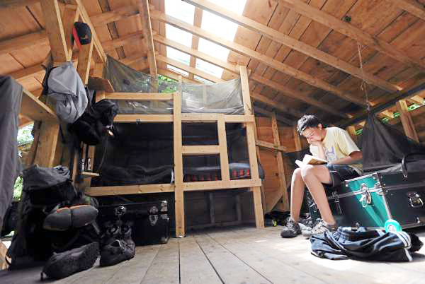 Patrick Meteer of Arlington, Mass. finds quiet time to read in a lean-to known as the Monkey House as other campers at Flying Moose Lodge swim in Craig Pond on Monday, July 19, 2010. The camp, started in 1921 offers boys between the ages of 10 and 16 a Maine summer camp experience without electricity. Meteer is a repeat camper. (Bangor Daily News/Kevin Bennett)