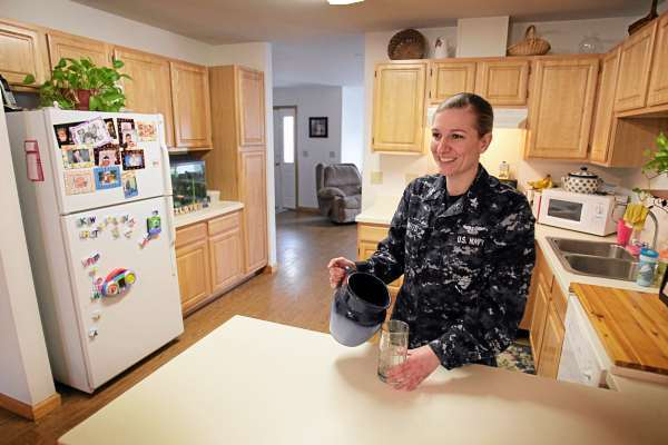 In this photo taken March 3, 2010, Autumn Swarts chats with a guest at her military housing at Brunswick Naval Air Base in Brunswick, Maine. Swats, a command career counselor, says she'll miss the niceties of her home, which includes radiant heat floors, when she leaves Brunswick. The base is scheduled to close in the upcoming months.  (AP Photo/Robert F. Bukaty)