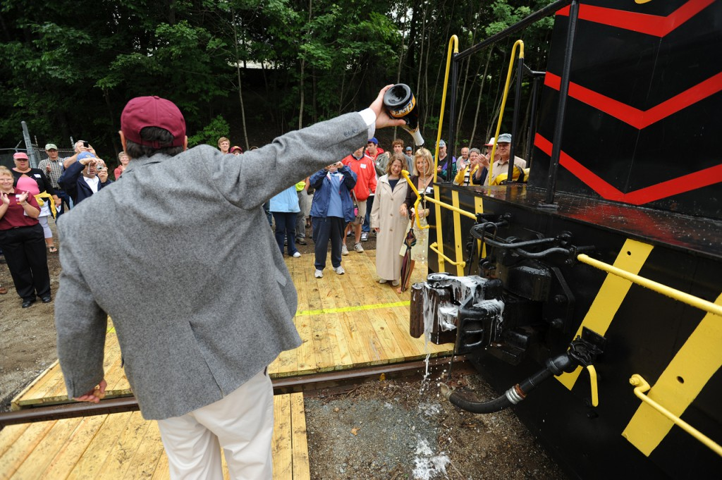 &quotMay God bless this train and all who ride on it.&quot said Downesat Rail Heritage Preservation Trust President Thomas Testa as her poured champagne over the #54 locomotive's coupling prior to the maiden run of the Downeast Scenic Railroad on Saturday, July 24, 2010 in Ellsworth. (Bangor Daily News/Kevin Bennett)