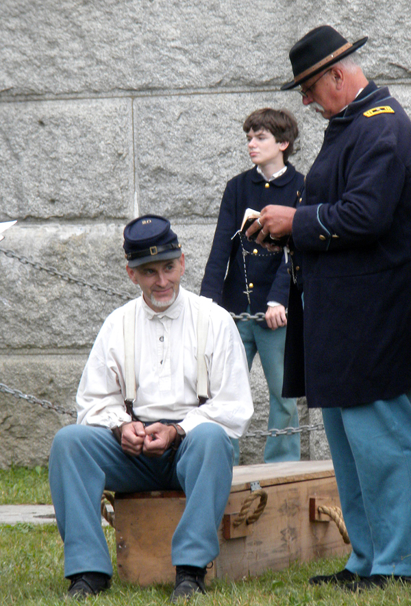 Cpl. Tim Brochu of the 20th Maine Company B sits on the edge of his casket Saturday as he listens to the charges of desertion lodged against him. The charges led to his execution by a firing squad during a Civil War reenactment event at Fort Knox over the weekend. Buy Photo