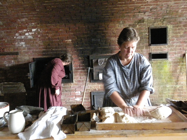 Sue Leighton of Orrington kneads bread dough Saturday in front of the brick ovens at Fort Knox in Prospect. Earlier this month, the ovens were fired up for cooking for the first time in more than a century. Leighton and her family lived across the road from the fort during her husband Michael's 12-year stint as park manager. He now is acting regional manager for the state Bureau of Parks and Lands. Buy Photo