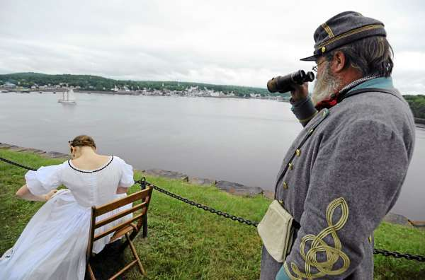 Ed Mann, right, of Aiken South Carolina watches the schooner Bowdoin from Ft. Knox in Prospect as Molly Faulkner of Old Saybrook CT. woks on embroidery during The Battle at Fort Knox on Saturday July 24, 2010. Mann came to the civil war reenactor event as a spectator but couldn't resist getting suited up the confederate solider he plays when in South Carolina as part of Hardee's Brigade South Guard. (Bangor Daily News/Kevin Bennett)