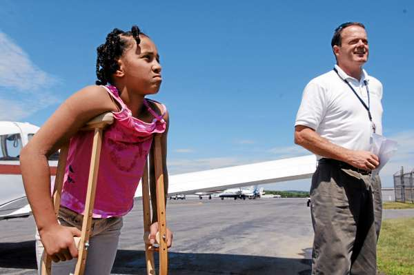 Camara Johnson, an 11-year-old Woodland girl, walks to the general aviation terminal at BIA after an Angel Flight piloted by Dan Herrick, right, brought her from Caribou for a medical appointment related to a bone deformity in her foot on Wednesday, July 21, 2010. Bangor Daily News/Scott Haskell)
