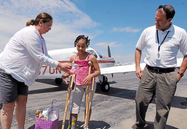 Camara Johnson, 11, of  Woodland, center, and her mother, Cherie Nichols, left, head off to a medical appointment for the girl after an Angel Flight  from Caribou to Bangor International Airport piloted by Dan Herrick, right, who is also a Bangor policeman, Wednesday, July 21, 2010.  Johnson has made almost 20 Angel Flights in the past two years as doctors tend to a bone deformity in her foot. (Bangor Daily News/Scott Haskell)
