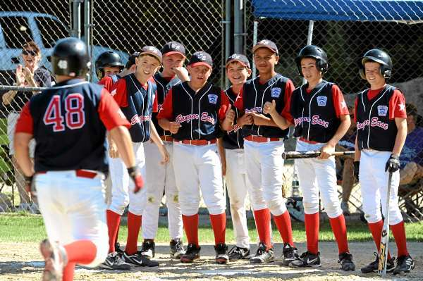 The Bangor East Little League team waits at homne plate for Tyler Mallory-MacDonald after he hit a home run during the 3rd inning in Hampden against Camden-Rockport on Tuesday, July 27, 2010. (Bangor Daily News/Kevin Bennett)
