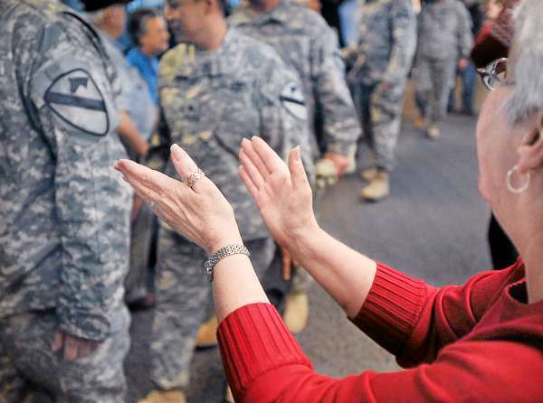 Troop Greeter Cathy Czarniecki claps her hands in applause for the passing troops returning from the mideast as they disembark at Bangor International Airport, Bangor, Maine, Tuesday, Nov. 10, 2009. (AP Photo/Michael C. York)