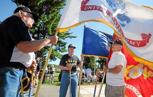 Korean War veterans Bernard Quinn (left) Joe King (center) and Bud Spellman hold flags of the different branches of the military as they prepare for the ceremony at the Maine Korean War Memorial in Bangor to commemorate the signing of the Korean War truce on July 27, 1953.  (Bangor Daily News/Gabor Degre)