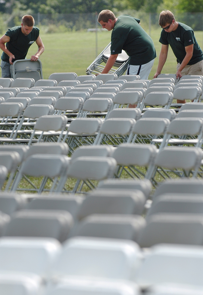 Ben Curtis (from left) Cameron Ciomei and Jake Taylor from Wallace Tent & Party Rentals out of Ellsworth help set up chairs in preparation for Celtic Woman, the first of the Hollywood Slots Waterfront Concert Series on the Bangor Waterfront on Wednesday, July 28, 2010. Taylor said the company set up &quotjust shy of 3400 chairs&quot for the event. (Bangor Daily News/Bridget Brown)