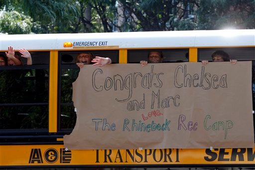 Children wave at members of the media from a bus decorated with a sign congratulating Chelsea Clinton and Marc Mezvinsky on Friday, July 30, 2010 in Rhinebeck, N.Y. (AP Photo/Mary Altaffer)