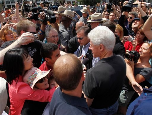 Former President Bill Clinton talks to people as he leaves a restaurant in Rhinebeck, N.Y., on Friday, July 30, 2010. Clinton made a long-anticipated appearance in the upstate New York village where his daughter is getting married tomorrow, drawing crowds of onlookers as preparations continued largely out of sight for the grand and secretive occasion.  (AP Photo/Mike Groll)