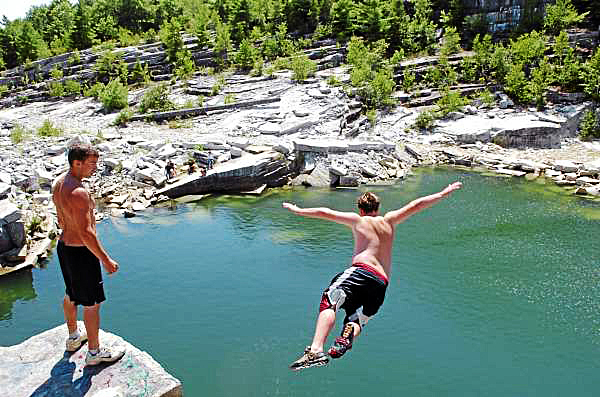 Ricky Palmer, 18, (left) of Winterport watches as Nick Adams, 16, of Frankfort jumps off a ledge at the Mt. Waldo Quarry on Sunday, Aug. 1, 2010, a popular swimming hole where a woman died Saturday. Amy Willey, 39, of Bucksport was killed when she jumped from a similar ledge and failed to resurface. &quotI hope they don't shut it down,&quot Adams said in between jumps Sunday. &quotWe swim up here all the time, all summer.&quot (Bangor Daily News/Bridget Brown)