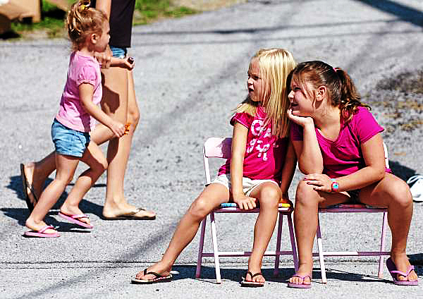 Hampden residents Kennedy Sharpe, 6, (left) and Taya Archer, 6, watch the parade in Winterport Saturday, July 31, 2010 in celebration of the town's 150th birthday. Festivities continue throughout the week and can be found at www.winterportmaine.gov. (Bangor Daily News/Bridget Brown)