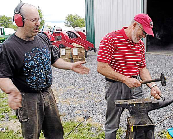 Using traditional blacksmithing techniques Herman Martin (left) of Laconia, New Hampshire, fashions a simple S-hook. Martin got a quick smithing lesson from Eugene Katsman, a blacksmith who set up his forge at the Northern Maine Fair this weekend to demonstrate the art of traditional metal work. (BANGOR DAILY NEWS photo by Julia Bayly)