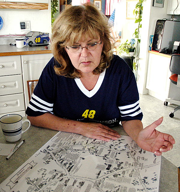 Sally Thibeault looks over the map she and a small group developed to accompany a reunion of anyone who lives or lived in the Flat Mountain area of St. Agatha. The event drew about 500 on Friday and was held in conjunction with the Long Lake Summerfest. (NEWS Photo by Julia Bayly)