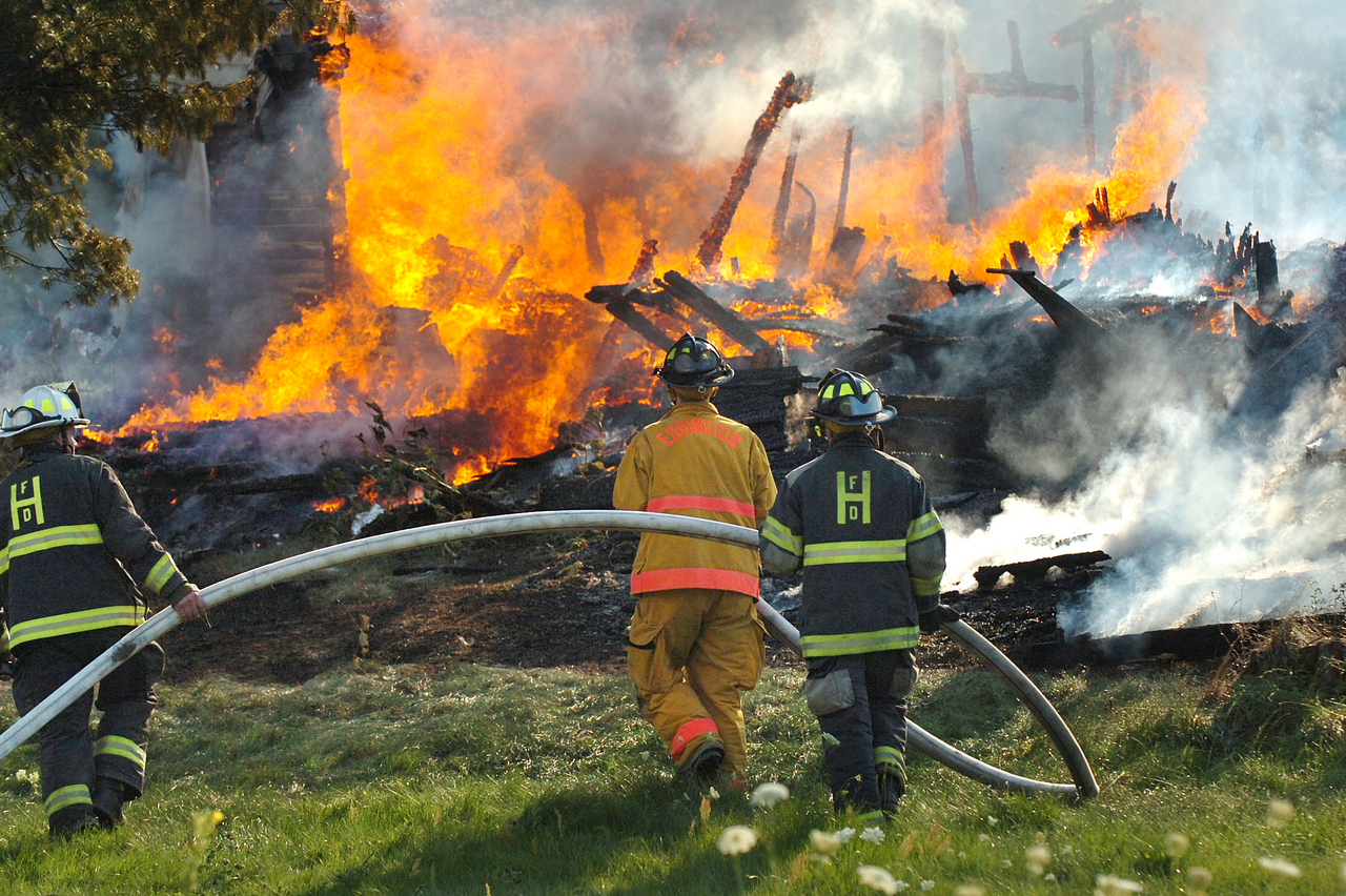 Firefighters including (from left) Capt. Tim True, Chris Dobson and Brent Basley work at the scene of a fire at the corners of Route 46 and Smithville Drive in Dedham on Sunday, Aug. 1, 2010. Multiple units responded to the scene and no one was injured in the blaze. (Bangor Daily News/Bridget Brown)