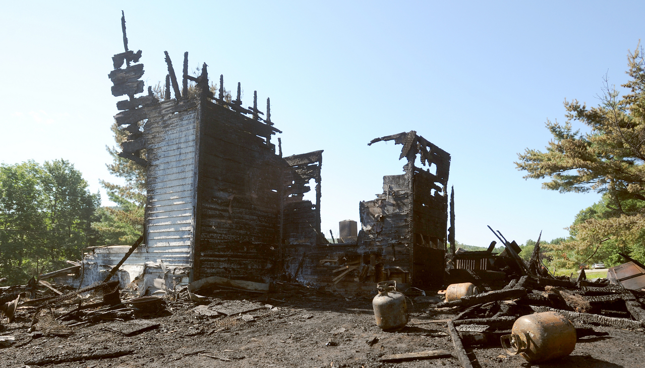 The remains of an 1800s farmhouse on Smithville Drive in Dedham on Monday morning, August 2, 2010 after it burned Sunday evening.  Adam Conners, 26, said that his brother,  Brett Conners, 33,  was home sleeping when he heard the fire alarm go off at 4:10 pm. Brett, who works nights, ran downstairs to find the house in flames and filled with smoke.  He was able to make it out of the burning building without injuries, but was unable to save any of his and his wife's, Joanne Bolduc, belongings.  &quotHe got out with the pair of shorts he was wearing everything else was burned,&quot Adam said.  The fire was so intense that it melted the siding on a mobile home about 50 yards away and the grass in a near by field caught on fire as exploding propane tanks sent burning debris flying. (Bangor Daily News/Gabor Degre)