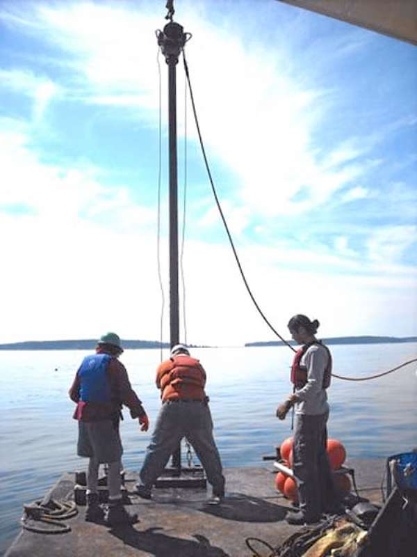 Dr. Joseph Kelley (left), Dr. Stefan Claesson (center) and Dr. Dan Belknap (right) deploying corer in Bass Harbor.  (Photo courtesy of Joe Kelley/University of Maine)  With Hewitt story about old tools find off Bass Harbor.