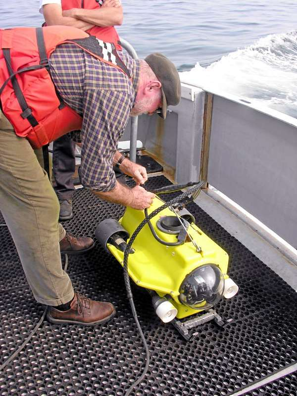 Dr. Lloyd Huff readying the underwater camera before dropping it over the drowned beach.(Photo courtesy of Joe Kelley/University of Maine) With Hewitt story about old tools find off Bass Harbor.