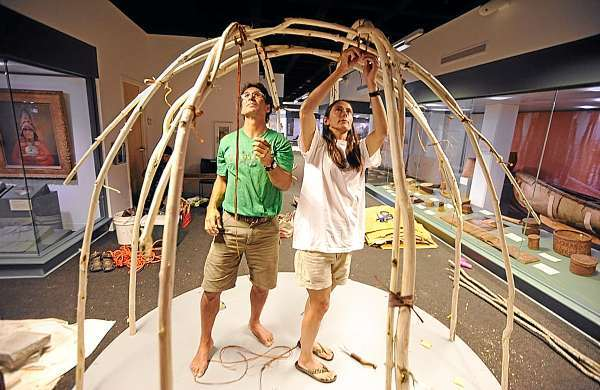 Barry and Lori Dana of Solon secure ash saplings for the internal structure of a wigwam they are helping to build at the Hudson Museum at the University of Maine in Orono. Photographed Monday afternoon, August 2, 2010. (Bangor Daily News/John Clarke Russ)