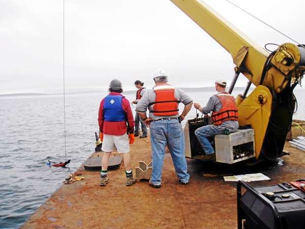Dr. Joseph Kelley (left), Dr. Dan Belknap (center), Dr. Stefan Claesson (right) and a student researcher (background) deploying vibracorer in outer Bass Harbor. The corer collected samples from a drowned lake/estuary complex associated with ancient stone tools. (Photo courtesy University of Maine)