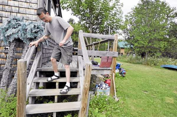 Using a railing for support, Dan Currit II hobbles down his outdoor steps in Unity Tuesday afternoon, August 3, 2010. In 2001 Currit's fateful leap at the Mount Waldo Quarry in Frankfort, Maine left him permanently disabled. He suffered numerous injuries including a broken back and shattered ankles. (Bangor Daily News/John Clarke Russ)