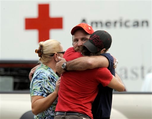 People comfort each other at Manchester High School, a staging area set up after a gunman killed multiple victims at the Hartford Distributors warehouse in Manchester, Conn., Tuesday, Aug. 3, 2010. (AP Photo/The Day, Tim Martin)