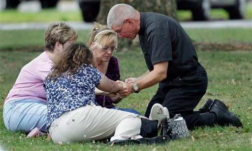 A priest kneels in prayer with three women outside Manchester High School, a gathering point for the families, co-workers and friends of shooting victims in Manchester, Conn., Tuesday, Aug. 3, 2010.  A warehouse driver who was asked to resign his job at a beer distributor refused, then opened fire Tuesday morning, a company executive said. Police said the gunman and several other people were killed and others were wounded. (AP Photo/Charles Krupa)
