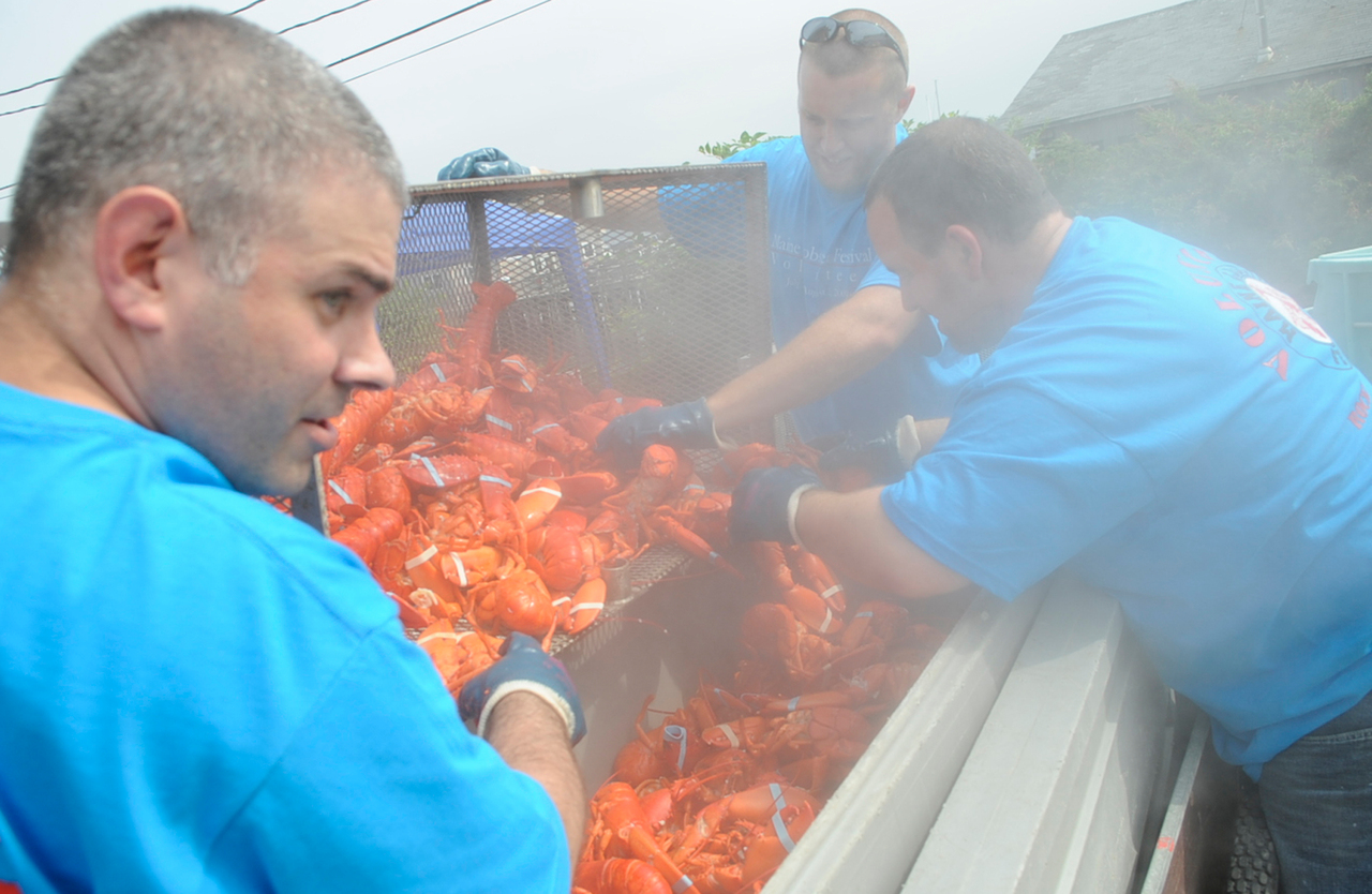 Andy Derochers (from left), Josh Cross and Ryan Morris, all local volunteers from Bank of America, get lobsters ready for transport to the Maine Food Tent after 12 minutes of steaming during opening day at the Maine Lobster Festival on Rockland's waterfront on Wednesday. The 62nd Maine Lobster Festival runs through Sunday.  (BANGOR DAILY NEWS PHOTO BY JOHN CLARKE RUSS)  CAPTION  Left to right: Andy Derochers,  Josh Cross and Ryan Morris, all local volunteers from Bank of America,  get lobsters ready for transport to the Maine Food Tent after 12 minutes of steaming during opening day at the Maine Lobster Festival on Rockland's waterfront Wednesday, July 29, 2009. The 62nd Maine Lobster Festival runs through Sunday, August 2. (Bangor Daily News/John Clarke Russ)