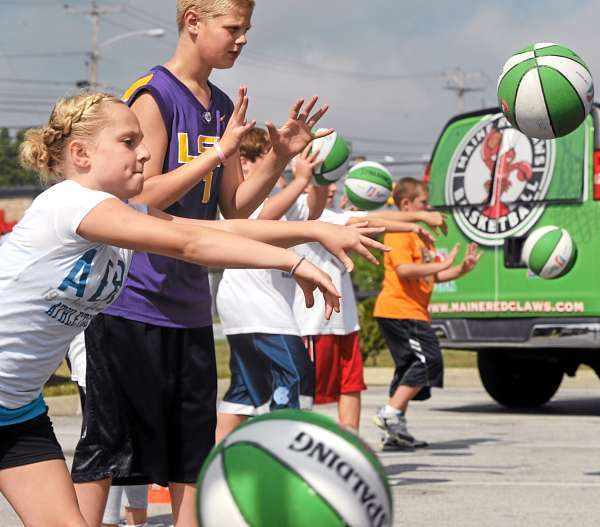 Elizabeth White, 11, of Veazie, (left) and Sam Brown, 14, of Lee were among the approximately 25 kids who participated in the Maine Red Claws basketball clinic held at the Dunkin Doughnuts parking lot in Brewer Wednesday. (Bangor Daily News/Gabor Degre)