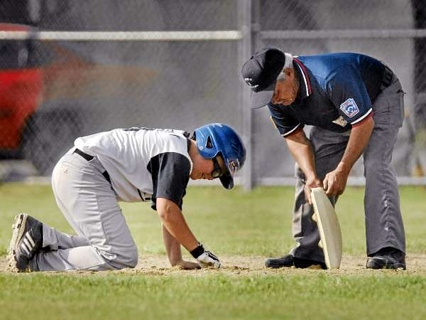 Waldo County All Star Alex McKenney helps second base umpire Eddie Parra repair the base after overturning it on a slide in the third inning of their game versus the York County All Stars in Bucksport, Wednesday, August 4, 2010. Bangor Daily News/ Michael C. York