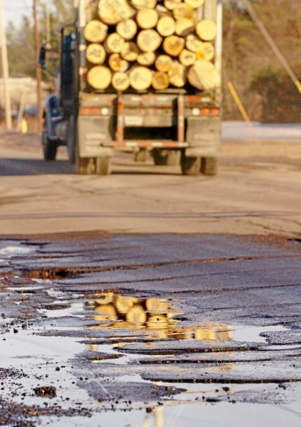 Reflected in the puddles of a potholed section of Route 2 in Hermon, a log truck hauls its load east toward Bangor on Monday. Safety groups are saying that increased log truck weights allowed by an emergency bill enacted last month will likely increase infrastructure problems on Maine highways.  (BANGOR DAILY NEWS PHOTO BY GABOR DEGRE)  CAPTION Reflected in the puddles of a potholed section of Route 2 in Hermon, a log truck hauls its load east toward Bangor on Monday, Feb. 4, 2008.  Safety groups are saying that increased log truck weights allowed by an emergency trucking bill will likely increase infrastructure problems on Maine highways.  (Bangor Daily News/Gabor Degre)