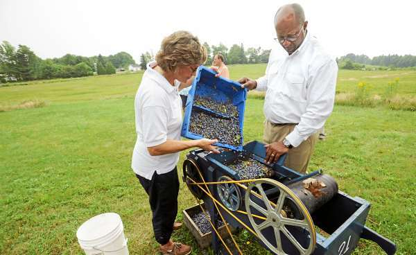 U.S. Trade Representative  Ron Kirk (right) watches as Annie Allen of G.M. Allen & Son demonstrates how the winnower works at the company's blueberry farm and processing center in Orland Thursday.   (Bangor Daily News/Gabor Degre)