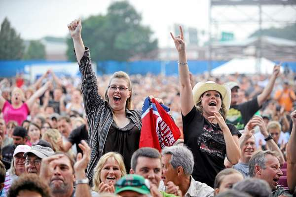 Skynyrd fans Rachel Malcolm, left of Trenton and friend Jamie Tate-Copeland whoop it up with thousands of others as Charlie Daniels arrives onstage for  the open act on Bangor's waterfront Thursday evening. (Bangor Daily News/ John Clarke Russ)