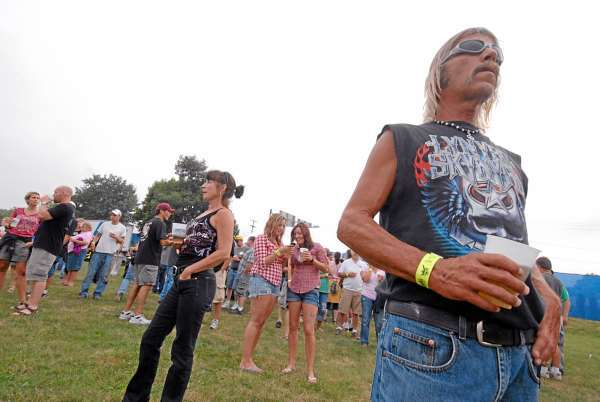 Mike Davis, 51 of Bangor takes in the scene at a packed Bangor warterfront concert venue before the start of Thursday evening's Charlie Daniels-Lynyrd Skynyrd line-up. Davis brought his girldfriend Sonya Gordon ( not pictured) of Bangor for their 4-year anniversary. Davis said he brought his lighter in anticpation of Skynyrd playing &quotFree Bird.&quot (Bangor Daily News/John Clarke Russ)