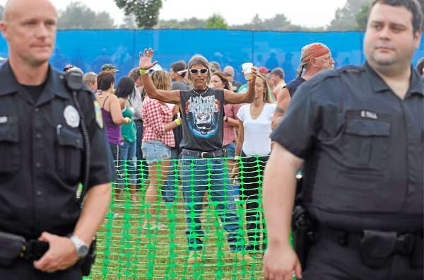 Mike Davis,center, 51,  of Bangor shows his excitement before the start of Thursday evening's Charlie Daniels-Lynyrd Skynyrd line-up. &quotI brought my lighter, &quot said Davis in anticipation of Skynyrd playing &quotFree Bird.&quot  In the foreground were Bangor Police Patrolman Edward Mercer, left and Detective Erik Tall (cq)(Bangor Daily News/John Clarke Russ)