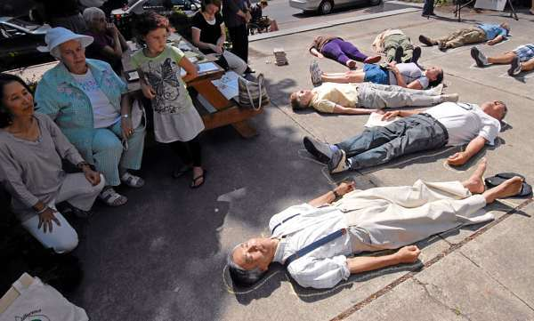 Lying on the pavement, Masanabu Ikemya (in foreground) of Bar Harbor and others participated in a symbolic &quotdie-in&quot during Friday afternoon's Hiroshima Commemoration at  Pierce Park next to Bangor Public Library. On the far left (kneeling) was Ikemya's wife Tomoko Ikeyima later read a childrens' picture card story with her husband regarding the Hiroshima bombing in 1945. (Bangor Daily News/John Clarke Russ)